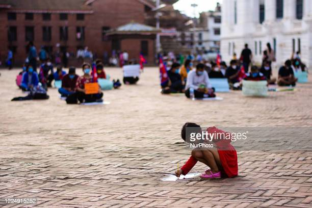 Girl is pictured playing with water pothole during a protest at Kathmandu, Nepal on Monday, July 6, 2020.