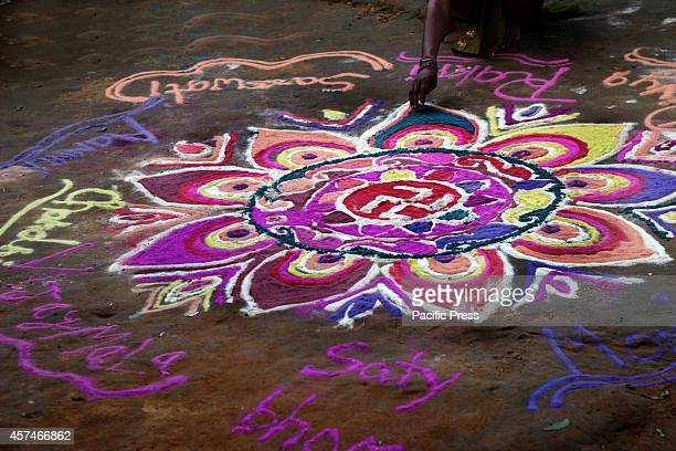 A girl is preparing the 'Rangoli' before the Diwali festival at Allahabad People clean renovate and decorate their homes before Diwali festival will...