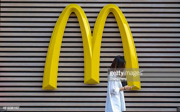 A girl is reading her mobile phone walking past the huge logo on the exterior wall of a McDonalds restaurant in Shenyang downtown Huge logo of...