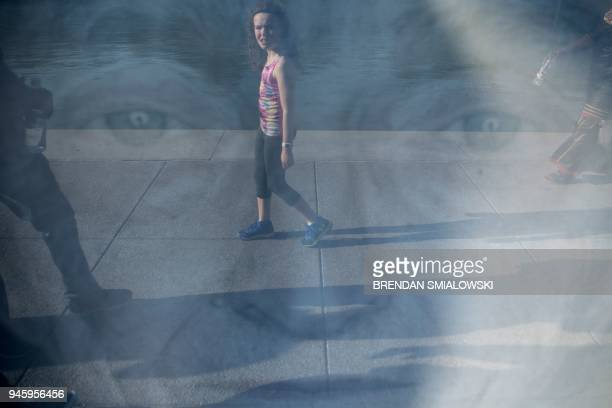 A girl is reflected in a portrait of a Holocaust survivor during the Lest We Forget exhibition along the Reflecting Pool at the National Mall on...
