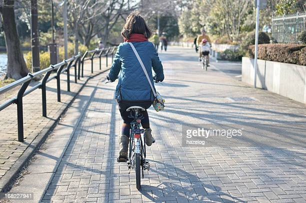 Girl is riding a bike in the park road.