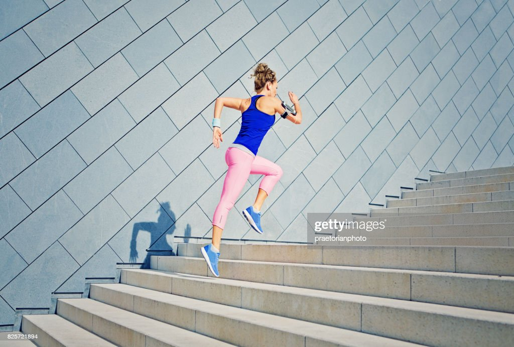 Girl is runing on the city stairs and listening the music : Stock Photo