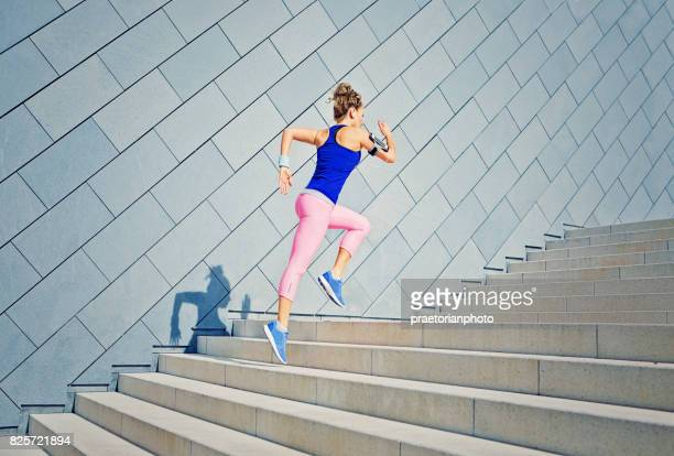 girl is runing on the city stairs and listening the music - donne immagine foto e immagini stock