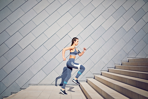 Girl is runing on the city stairs and listening the music 868169994