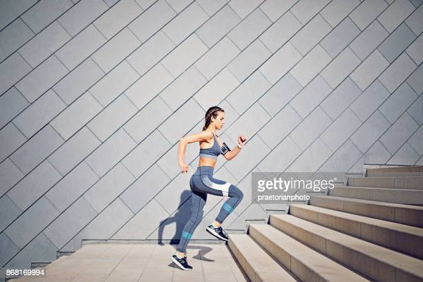 girl is runing on the city stairs and listening the music - sports clothing stock pictures, royalty-free photos & images