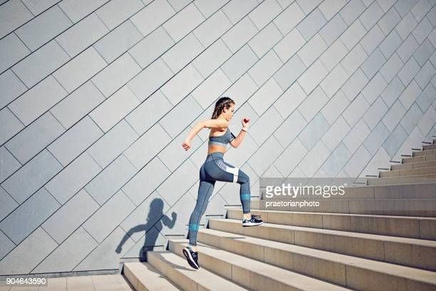 Girl is running on the city stairs and listening the music