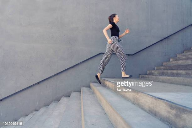 girl is running on the city stairs in front of a concrete wall - staircase stock pictures, royalty-free photos & images