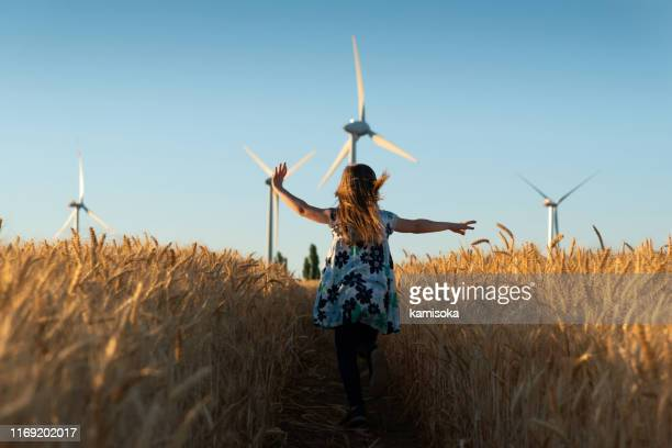 girl is running the way to wind energy - la via giusta foto e immagini stock