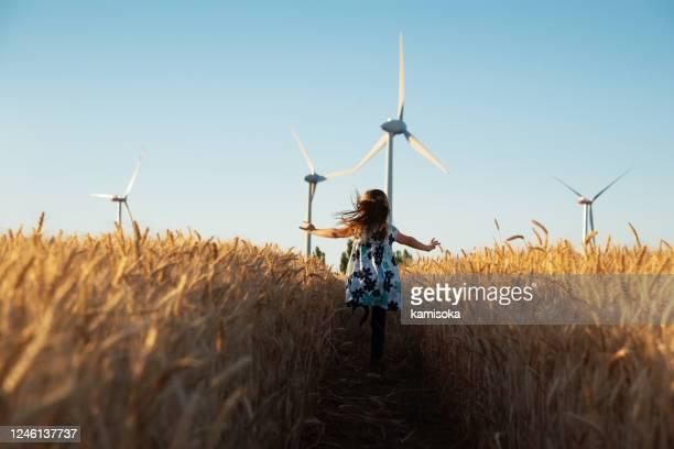het meisje loopt de manier aan windenergie - visie stockfoto's en -beelden