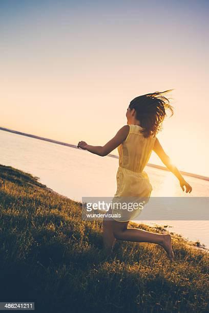 Girl is running through grass at lake