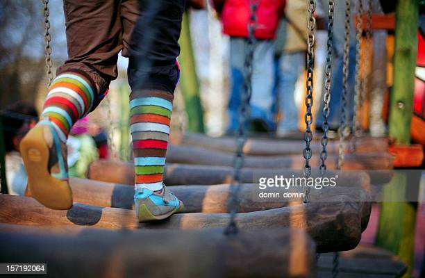 Girl is running through the wooden bridge on children playground