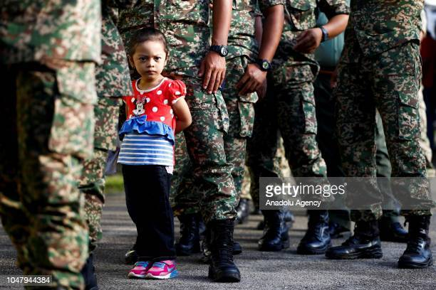 A girl is seen accompanying her father during early voting for the Port Dickson Parliament byelection at the Army Basic Training Centre in Port...