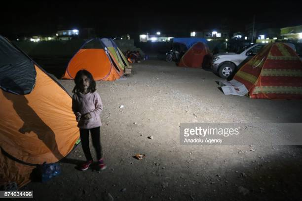 A girl is seen as she and other people sit outside as a precaution during night at Darbandikhan district of Suleymaniyah after an earthquake...