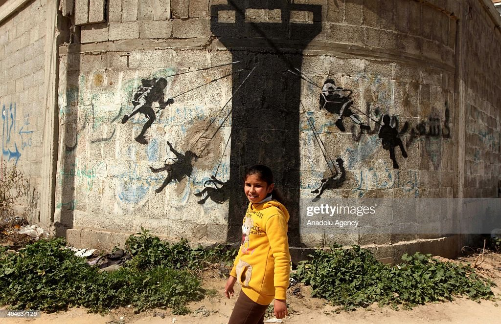 A girl is seen in front of a graffiti on a wall of a building drawn by British artist Banksy in Beit Hanoun, Gaza on February 27, 2015. Famous British artist Banksy visited Gaza and drew graffiti on the walls of houses in Beit Hanoun destroyed in Israel's recent attacks on Gaza.