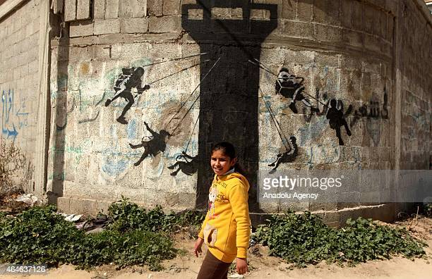 A girl is seen in front of a graffiti on a wall of a building drawn by British artist Banksy in Beit Hanoun Gaza on February 27 2015 Famous British...