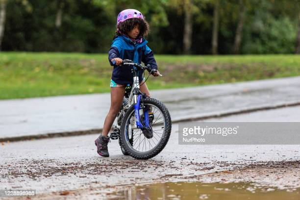 A girl is seen on her bicycle on a rainy cold Sunday in Dulwich Park in South London England on October 4 2020