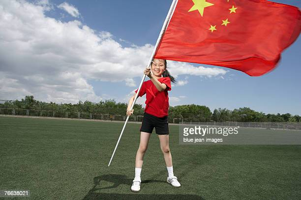 A girl is shaking the Chinese flag.