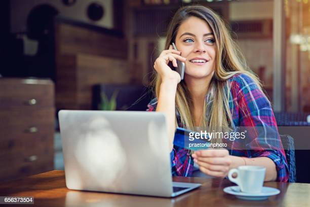 Girl is shopping online and calling card support for help