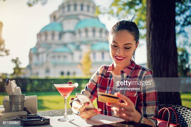 girl is shopping online using her mobile phone and credit card in a cafe - bulgarian girl stock photos and pictures
