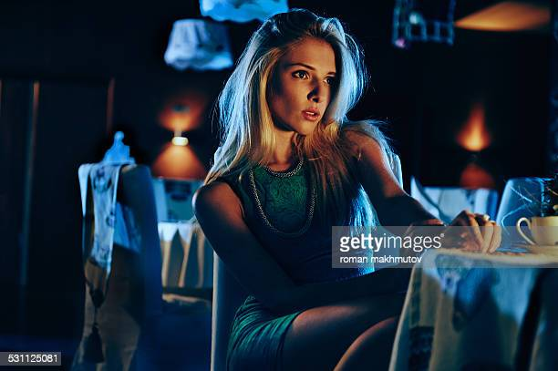 Girl is sitting in a bar and having a cup of coffe