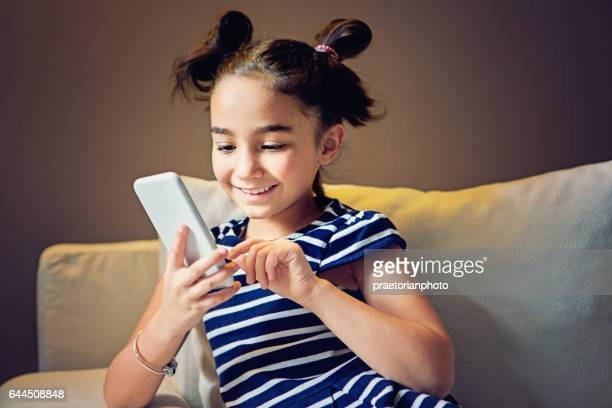Girl is sitting on the sofa and texting