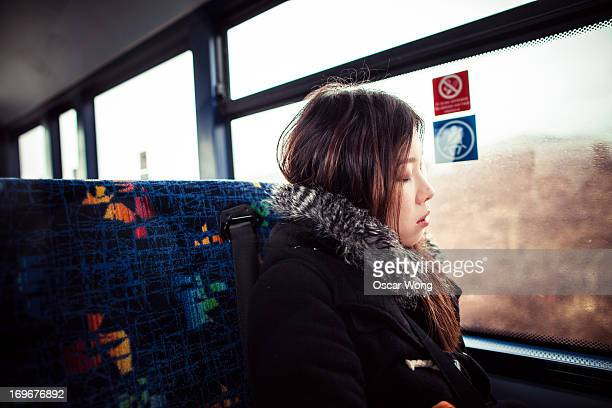A girl is sleeping on the bus