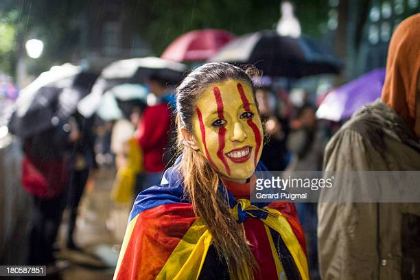 Girl is standing in a demonstration to claim for Catalonia independence during the National Day in Downing Street, London. She is smiling and wearing...