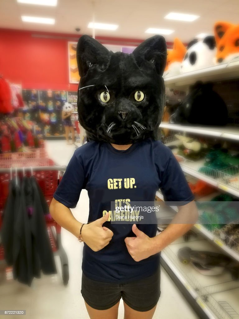 A girl is standing in a store wearing a funny black cat mask : Stock Photo