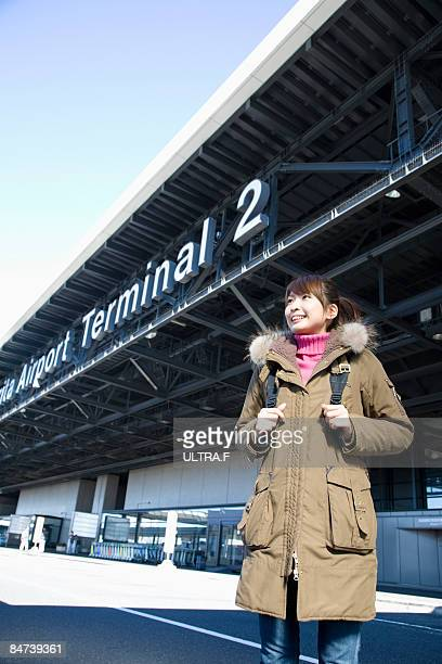 A girl is standing in front of an airport.
