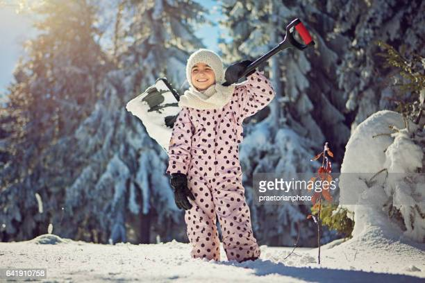 Girl is standing in the forest with the shovel