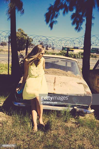 Girl is standing next to an oldtimer car (retro)