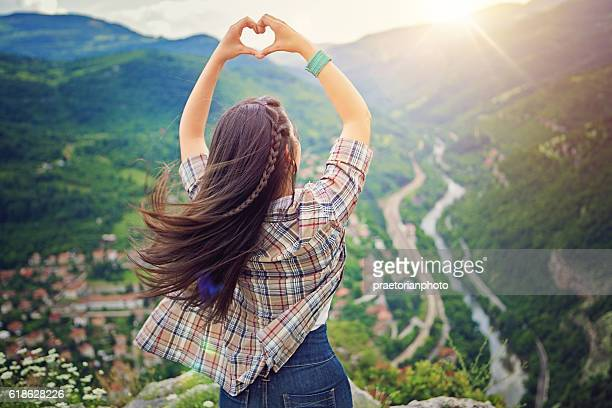 Girl is standing on the edge and making heart sign