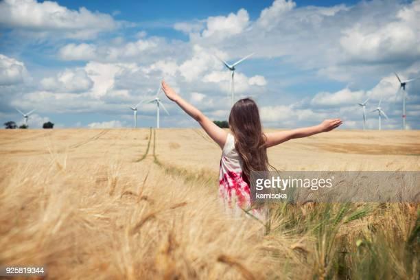 flickan står mot vindkraftverk - vindsnurra jordbruksbyggnad bildbanksfoton och bilder