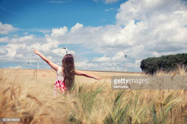 girl is standing towards wind turbines - vento foto e immagini stock