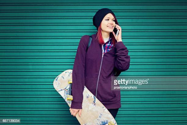 Girl is standnding to the wall and talking using her mobile phone