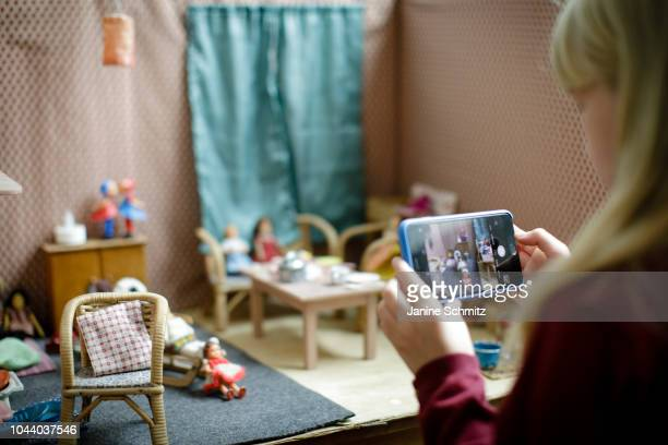 A girl is taking a picture of her dollhouse with a smartphone on August 14 2018 in Berlin Germany