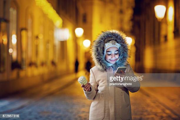 Girl is texting in night streets of old town and eating marshmallow