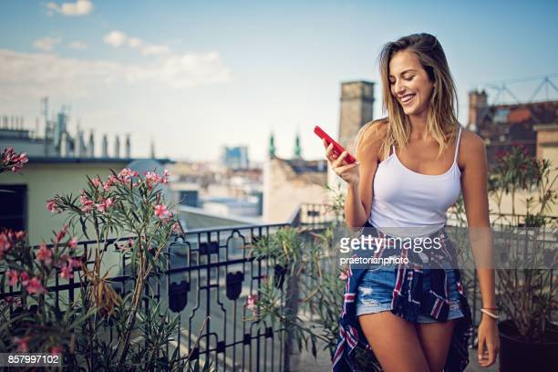 Girl is texting on the roof terrace