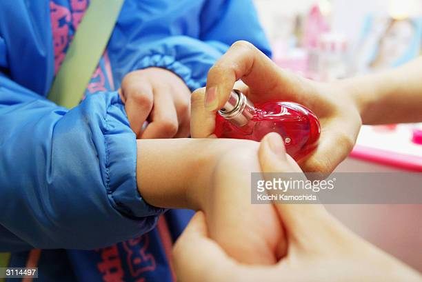A girl is tries perfume with the help of a sales assistant at a store of the Japanese toy maker Bandai Co Ltd on March 20 2004 in Tokyo Japan Bandai...