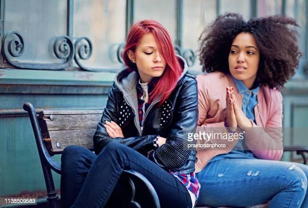 la fille essaye de calmer sa petite amie bouder - ados lesbiennes en couple photos et images de collection