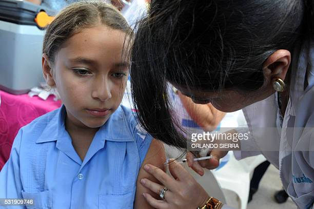 A girl is vaccinated against the human papilloma virus by Health Ministry employees in Tegucigalpa on May 17 2016 The government wants to inmunize...