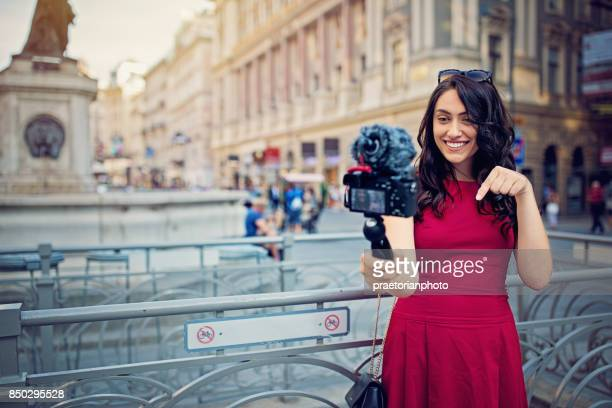Girl is vlogging in the pedestrian zone of the city center