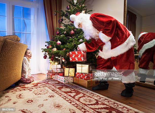 Girl is watching father christmas bring presents.