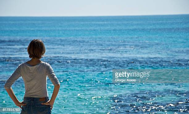 A girl is watching the ocean.