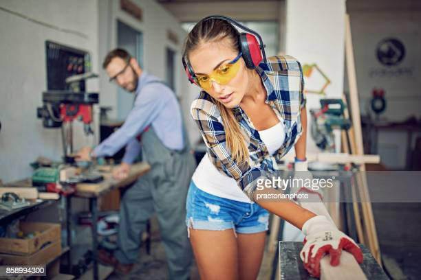 Girl is working with machinery and timber in a small family carpenter factory