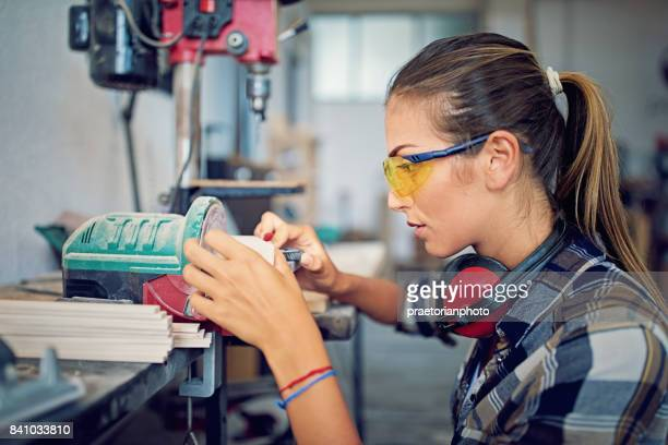 Girl is working with machinery in a small family carpenter factory