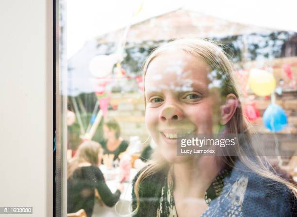 Girl joking with her nose against a window