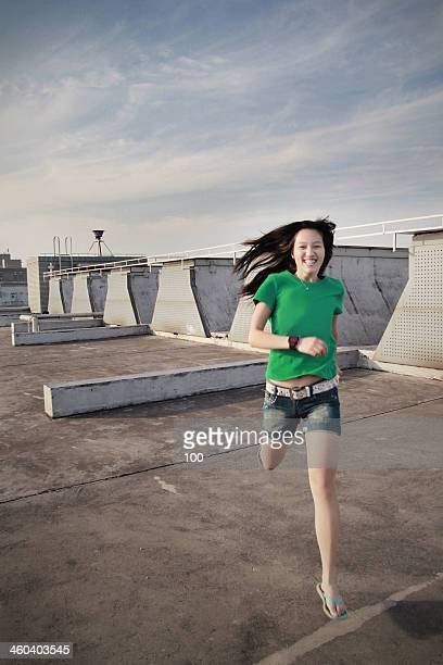 girl jump on the rooftop - short sleeved stock pictures, royalty-free photos & images