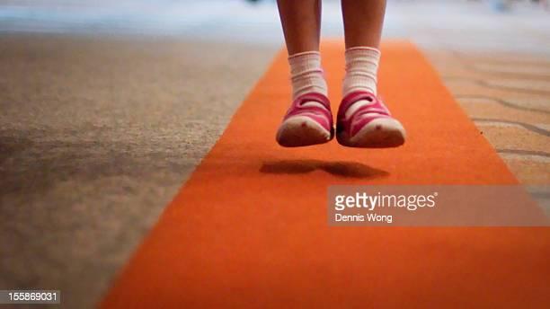girl jump over orange carpet - orange shoe stock photos and pictures