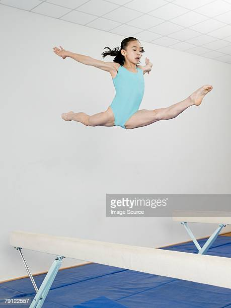 Girl jumping above balance beam